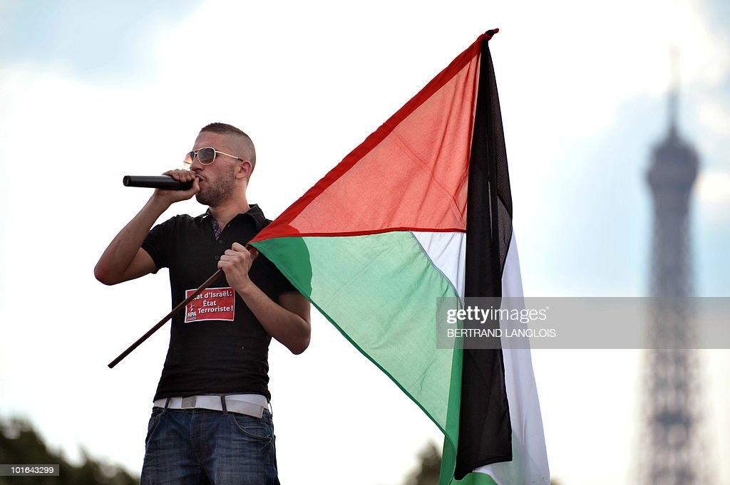 A demonstrator speaks as he carries a Palestinian flag during a protest in front of the Eiffel Tower on June 5, 2010 in Paris streets against Israeli's storming of a Gaza-bound aid flotilla that left nine pro-Palestinian activits dead. The European Union will present in the coming days a proposal for lifting the Israeli blockade of Gaza, following the deadly raid this week on aid ships bound for the Palestinian territory, Spain's foreign minister said toady.