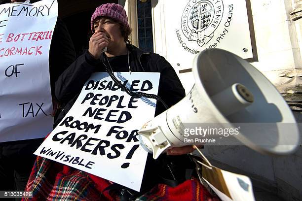 A demonstrator speaks into a microphone while holding a placard with the slogan 'Disabled People Need Room For Carers' outside The Supreme Court...