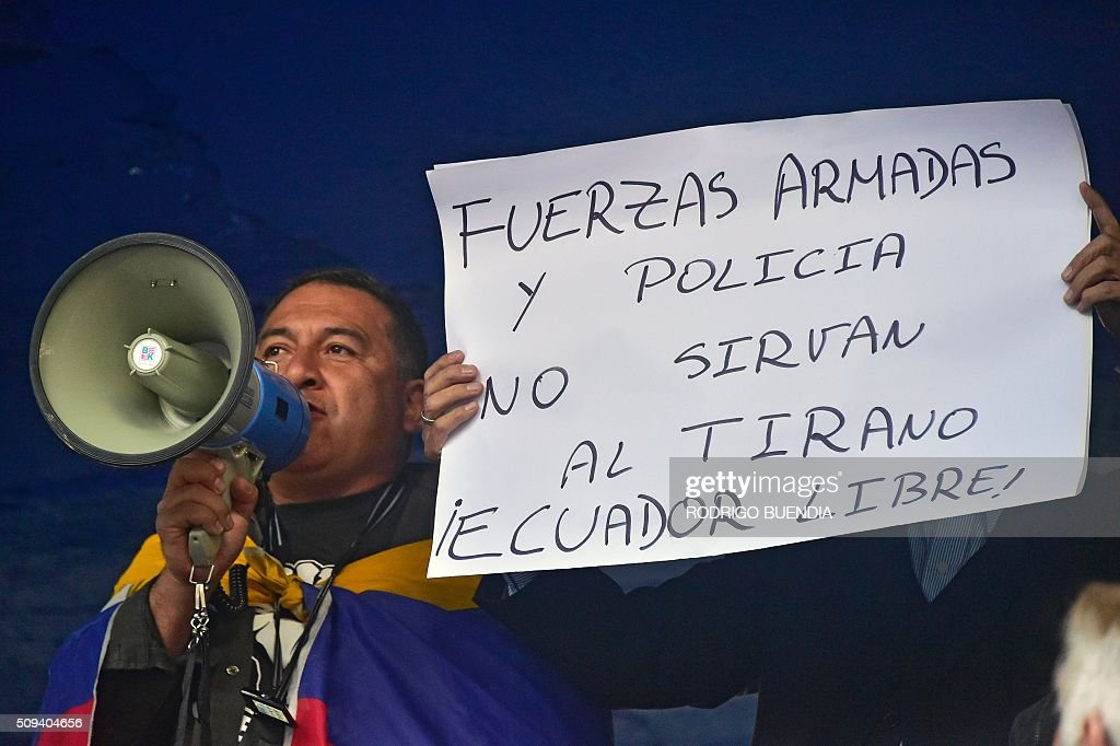 A demonstrator speaks on a megaphone next to a sign reading 'Armed Forces and Police, don't serve the tyrant. Free Ecuador!' during a protest against Ecuadorean President Rafael Correa in Quito on February 10, 2016. AFP PHOTO / RODRIGO BUENDIA / AFP / RODRIGO BUENDIA