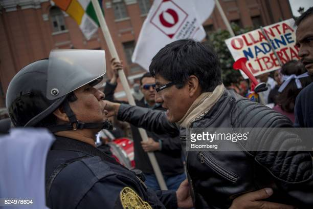 A demonstrator speaks with a police officer during a protest against the detention of former Peruvian President Ollanta Humala and his wife Nadine...