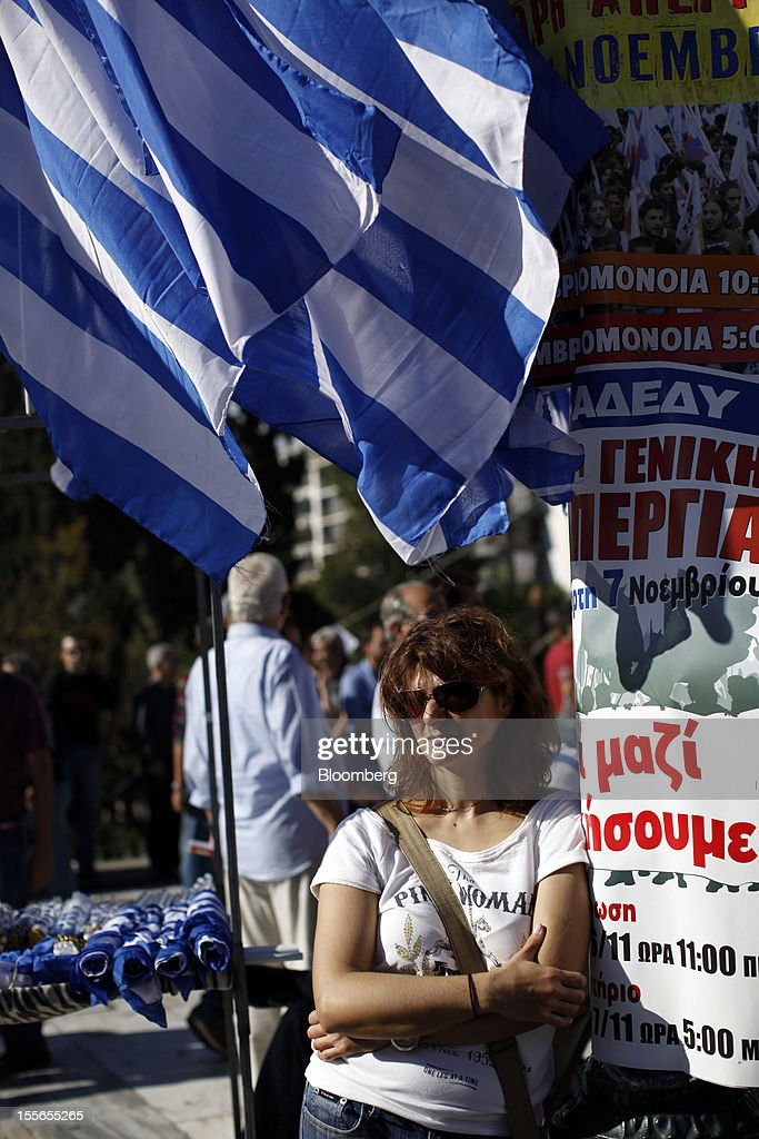 A demonstrator stands beneath a Greek national flag during a general strike protest in Athens, Greece, on Tuesday, Nov. 6, 2012. Greece headed for a cliffhanger vote on austerity measures needed to keep the bailout on track as a 48-hour general strike began and European officials squabbled over the timing of a deal to unlock rescue funds. Photographer: Kostas Tsironis/Bloomberg via Getty Images