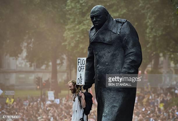 A demonstrator stands by a statue of former British Prime Minister Winston Churchill in Parliament square to hear speeches at the end of a protest...