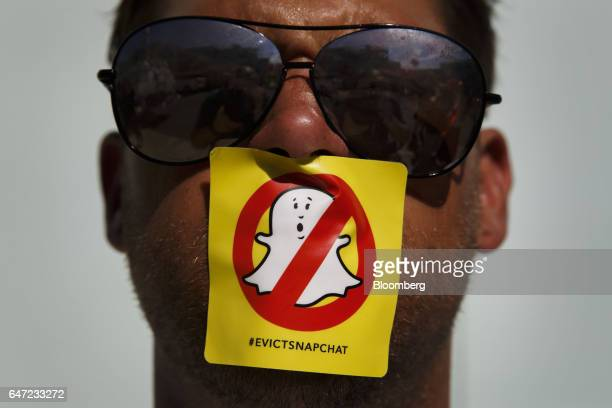 A demonstrator stands for a photograph with a '#evictsnapchat' sticker over his mouth while protesting outside the Snap Inc office in the Venice...