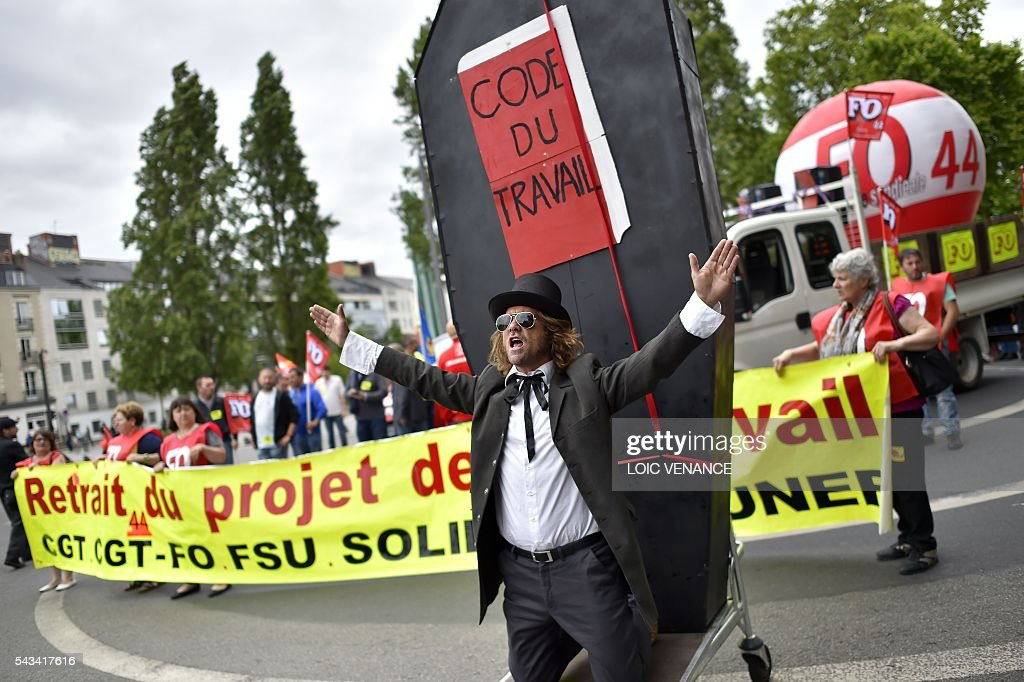 A demonstrator stands in front of a coffin with a placard reading 'Labour Code' during a protest against controversial labour reforms, on June 28, 2016 in Nantes, western France. People took to the streets in France on June 28 in the latest protest march in a marathon campaign against the French Socialist government's job market reforms. Last month the government used a constitutional manoeuvre to push the bill through the lower house without a vote in the face of opposition from Socialist backbenchers. / AFP / LOIC