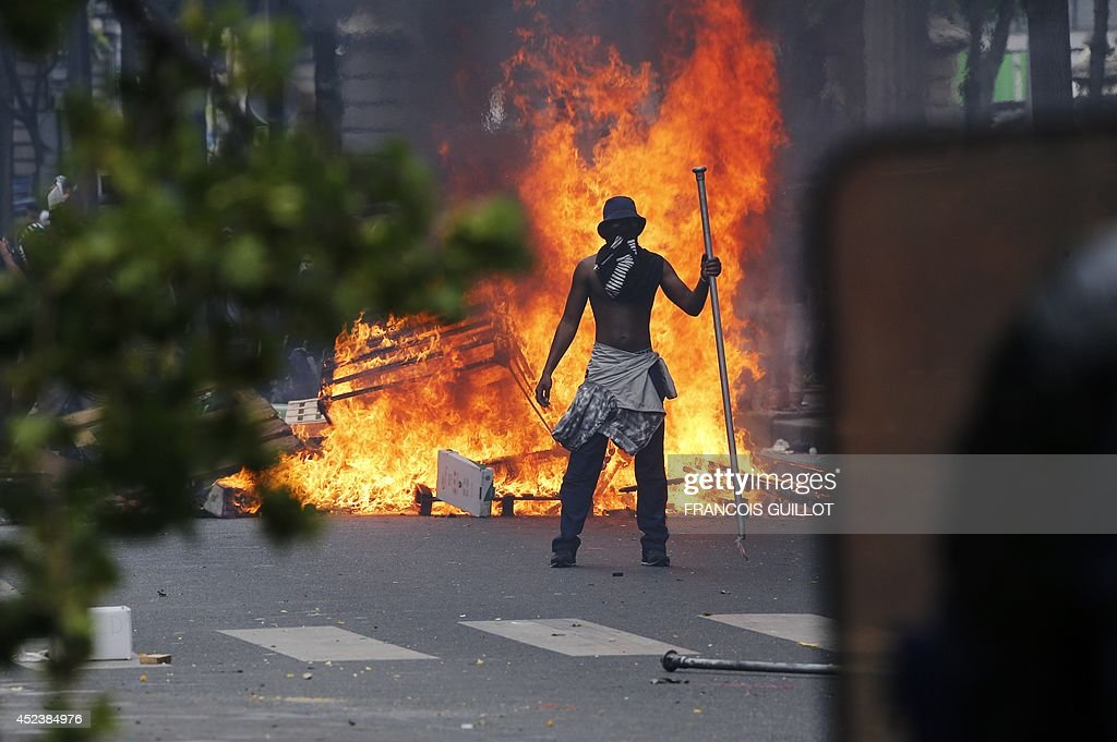 A demonstrator stands in front of a fire barricade near the aerial metro station of Barbes-Rochechouart, in Paris, on July 19, 2014, during clashes with French riot police in the aftermath of a demonstration, banned by French police, to denounce Israel's military campaign in Gaza and show support to the Palestinian people. Demonstrators threw rocks and bottles at anti-riot squads blocking their route, who responded with tear gas lobbied into the streets.