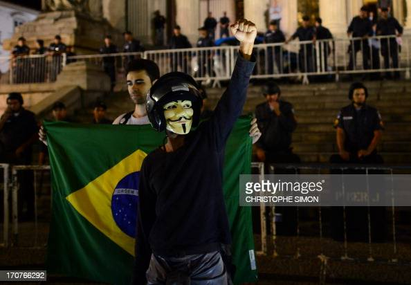 A demonstrator takes part in a march in downtown Rio de Janeiro on June 17 to protest against higher public transportation fares and the use of...