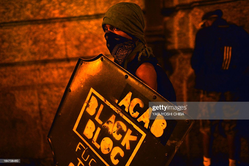 A demonstrator takes part in the 'Teachers' day' protest, demanding better working conditions and against police violence, on October 15, 2013 in Rio de Janeiro, Brazil.