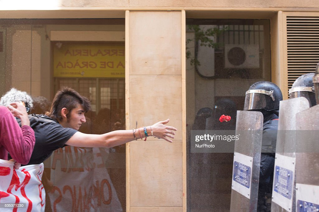 Demonstrator throwing a flower because of the eviction of an squatted bank in Barcelona on May, 29 of 2016.