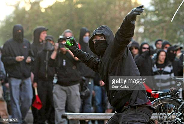 A demonstrator throws a bottle at riot police during clashes during a May Day march by leftwing protesters in Kreuzberg on May 1 2009 in Berlin...
