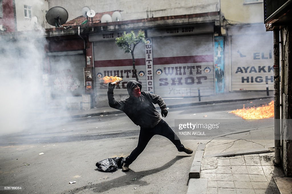 A demonstrator throws a molotov cocktail during a May Day rally in the Okmeydani neighbourhood of Istanbul on May 1, 2016. Turkish police clamped down on unauthorised protests during a tense May Day in Istanbul, using tear gas and water cannon against demonstrators and imposing a heavy security blanket on the city. / AFP / YASIN