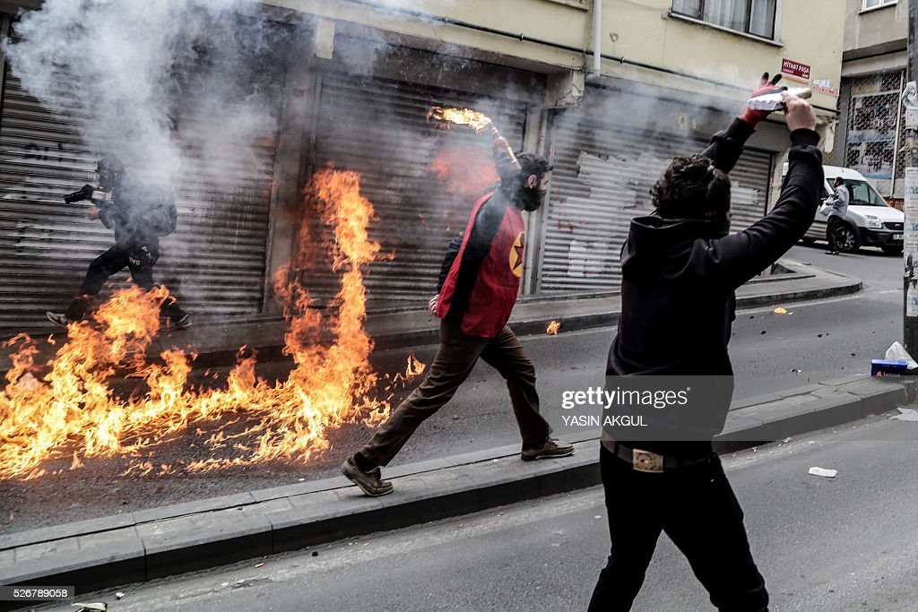 A demonstrator (L) throws a molotov cocktail during a May Day rally in the Okmeydani neighbourhood of Istanbul on May 1, 2016. Turkish police clamped down on unauthorised protests during a tense May Day in Istanbul, using tear gas and water cannon against demonstrators and imposing a heavy security blanket on the city. / AFP / YASIN