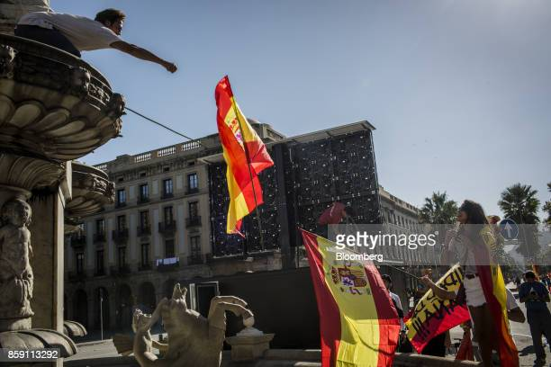 A demonstrator throws a Spanish national flag during a protest for Spanish unity at the Pla de Palau square in Barcelona Spain on Sunday Oct 8 2017...