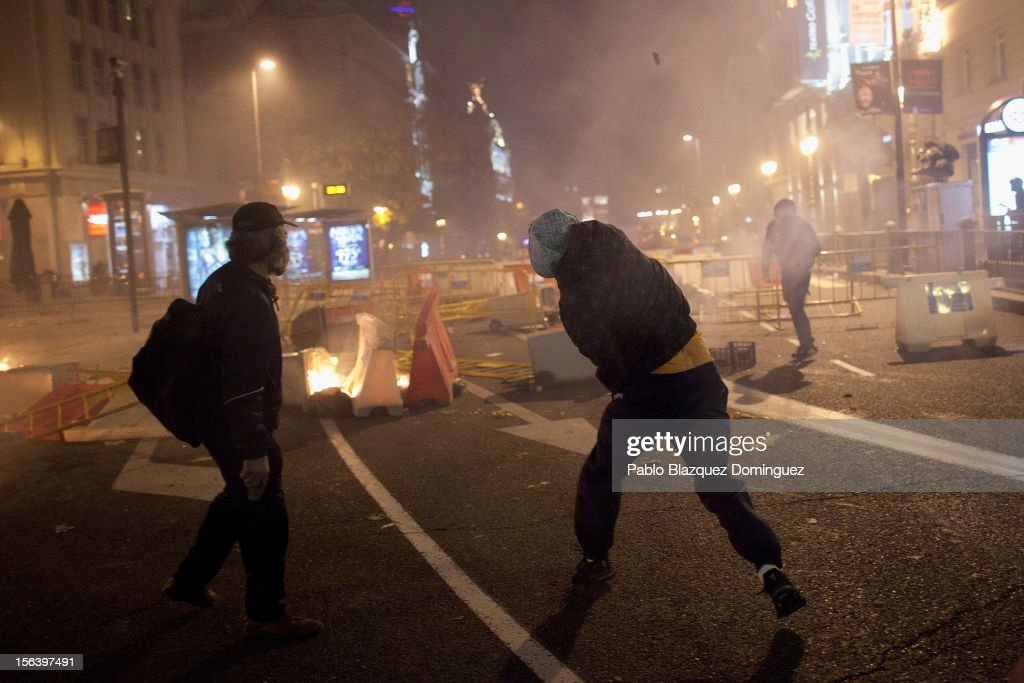 A demonstrator throws a stone at riot police after a demonstration near the Spanish parliament turned violent on November 14, 2012 in Madrid, Spain. A coordinated general strike by unions in Spain and Portugal has paralysed public transport in the two countries with further strikes planned across Europe. The strike against the governments' austerity measures have force hundreds of flights to be cancelled and factories and ports to come to a standstill.