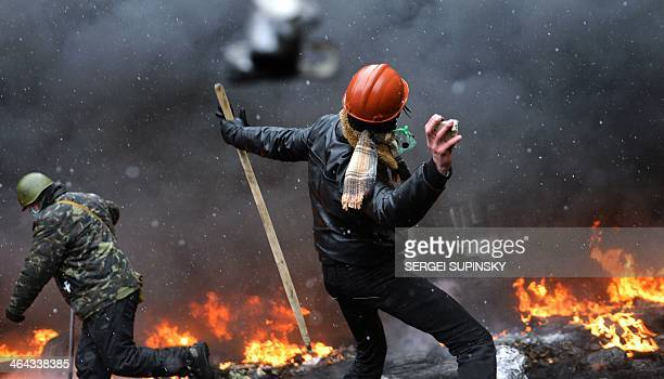 A demonstrator throws a stone during clashes between protestors and police in the center of Kiev on January 22 2014 At least two activists were shot...