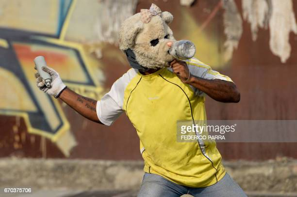 TOPSHOT A demonstrator throws back a tear gas canister at riot police during a march against Venezuelan President Nicolas Maduro in Caracas on April...