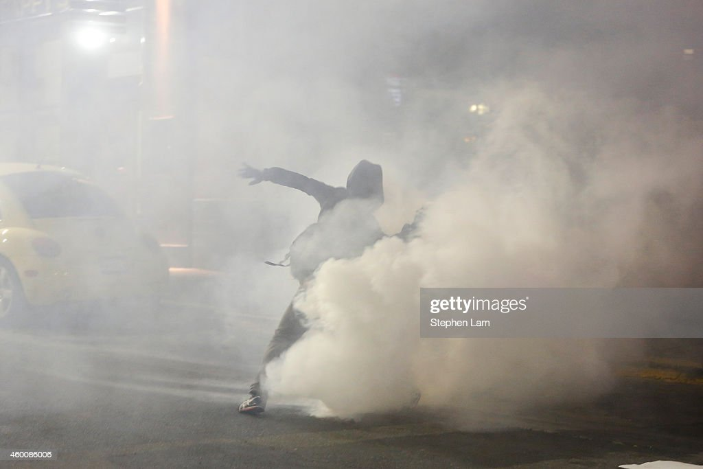 A demonstrator throws backs a teargas canister toward the police line during the fourth night of demonstrations over recent grand jury decisions in...