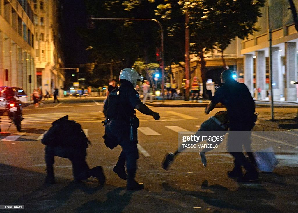 A demonstrator tries to escape from the riot police during clashes which erupted after a march by Brazilian workers in Rio de Janeiro on July 11, 2013 in a day of industrial action called by major unions to press demands for better work conditions. Demonstrators on Thursday blocked roads and staged protest rallies across the country on the 'National Day of Struggles' which was called by the country's five leading labour federations during last month's mass street protests to demand better public services and an end to endemic corruption.
