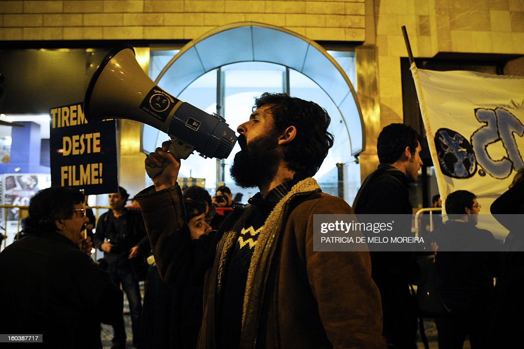 A demonstrator uses a loudspeaker to shout slogans outside the International Monetary Fund (IMF) headquarters in Lisbon on January 30, 2013, to protest against government's austerity measures imposed by the European Union and the IMF.