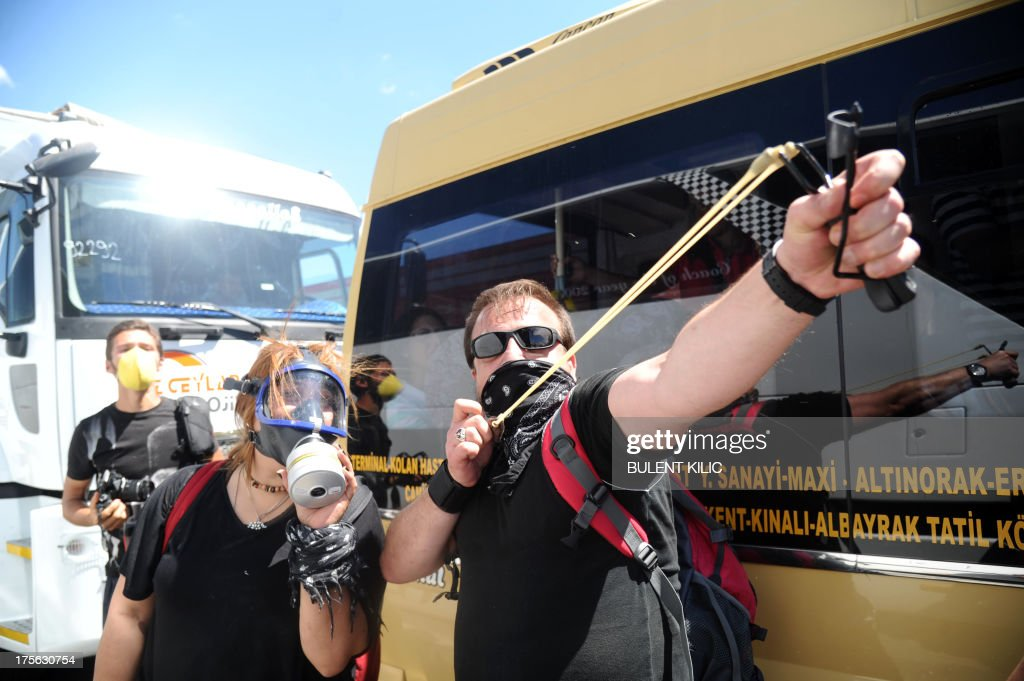 A demonstrator uses a sling shot during clashes between Turkish police and protestors on August 5, 2013, as police and gendarmerie block the way to a courthouse in Silivri, near Istanbul, where prosecutors are scheduled to deliver their final arguments in the case against 275 people accused of plotting to overturn the Islamic-leaning government. Among the defendants in the high-profile case -- seen as a key test in Prime Minister Recep Tayyip Erdogan's showdown with secularist and military opponents -- are ex-military chief Ilker Basbug and other army officers as well as lawyers, academics and journalists.