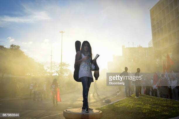 A demonstrator uses a smartphone while marching towards the National Congress during protests demanding the resignation of President Michel Temer in...