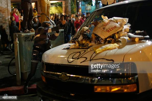 A demonstrator vandalizes a police car during the fourth night of demonstrations over recent grand jury decisions in policeinvolved deaths on...