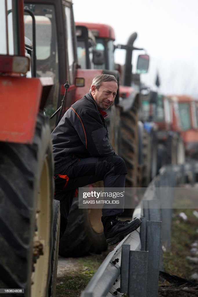 A demonstrator waits as farmers have parked their tractors near major motorways in Serres, north of Athens, on February 6, 2013, to protest against the cost of raw material they need for their production, such as petrol.