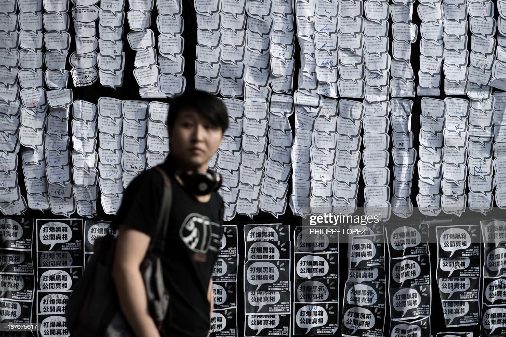 A demonstrator walks past a banner displaying leaflets signed in support of the HKTV broadcasting station wearing a mask looks on during a protest in support of HKTV in front of the government building in Hong Kong on November 6, 2013. The demonstrators protested against the government's decision to not grant a broadcasting license to HKTV, a station which promised high quality programming, in a move which they say will hamper the city's creative industry. The city's television airwaves are currently dominated by one broadcaster. AFP PHOTO / Philippe Lopez