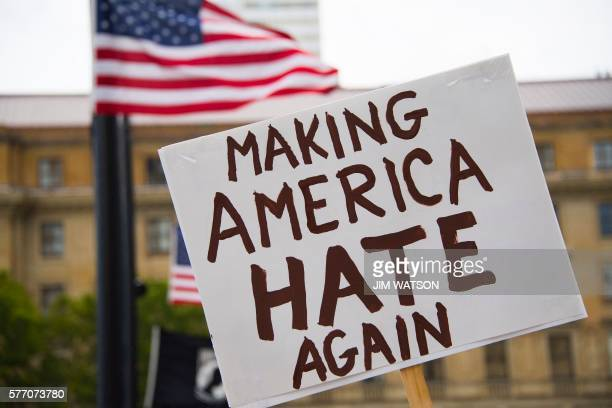 A demonstrator walks with a placard reading 'Making America Hate Again' during an antiDonald Trump rally in Cleveland Ohio near the Republican...