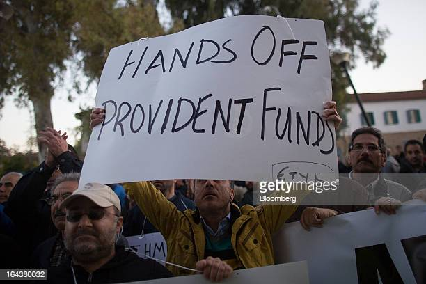 A demonstrator waves a banner reading 'Hands off provident funds' during a protest outside the Cypriot finance ministry by members of the bank union...