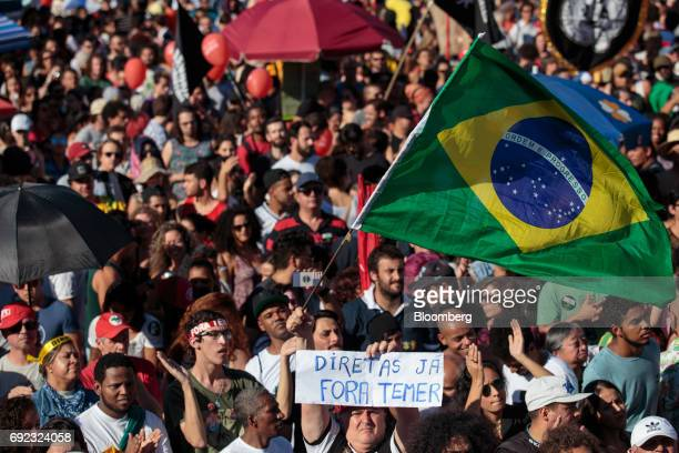 A demonstrator waves a Brazilian flag while holding a sign that reads 'Direct Elections Now Temer Out' during a protest against Brazilian President...