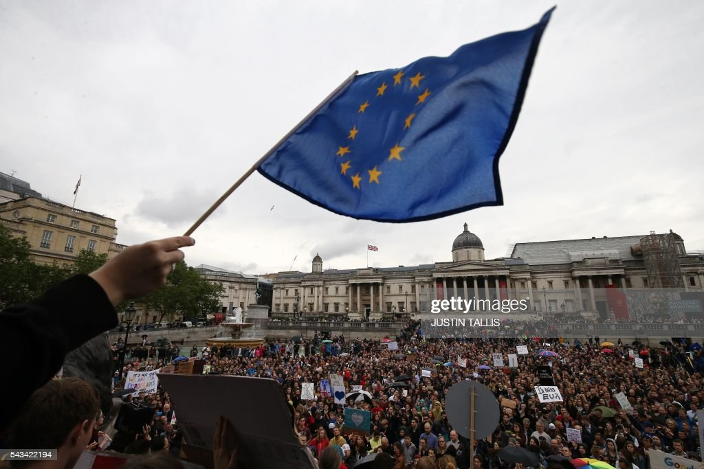 A demonstrator waves a European flag as people gather for an anti-Brexit protest in Trafalgar Square in central London on June 28, 2016. EU leaders attempted to rescue the European project and Prime Minister David Cameron sought to calm fears over Britain's vote to leave the bloc as ratings agencies downgraded the country. Britain has been pitched into uncertainty by the June 23 referendum result, with Cameron announcing his resignation, the economy facing a string of shocks and Scotland making a fresh threat to break away. / AFP / JUSTIN