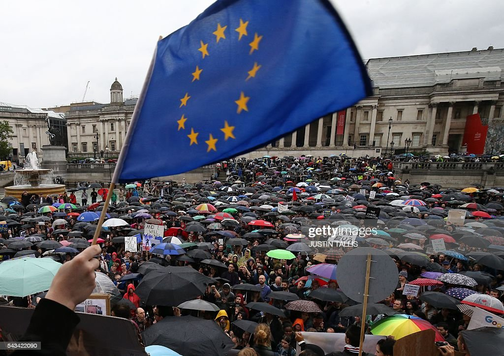 A demonstrator waves a European flag as people shelter under umbrellas at an anti-Brexit protest in Trafalgar Square in central London on June 28, 2016. EU leaders attempted to rescue the European project and Prime Minister David Cameron sought to calm fears over Britain's vote to leave the bloc as ratings agencies downgraded the country. Britain has been pitched into uncertainty by the June 23 referendum result, with Cameron announcing his resignation, the economy facing a string of shocks and Scotland making a fresh threat to break away. / AFP / JUSTIN