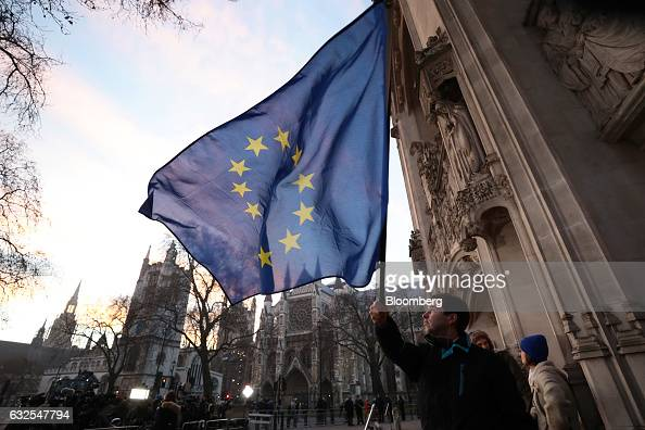 A demonstrator waves a European Union flag outside the Supreme Court in London UK on Tuesday Jan 24 2017 The court's 11 judges are due to give their...