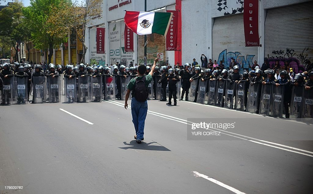 Demonstrator waves a Mexican flag in front of riot police during a protest against President Enrique Pena Nieto's reform agenda, on September 1, 2013, in Mexico City. At least two policemen were injured and four people were arrested after clashes with police during protests on Sunday in Mexico City against structural reforms promoted by Pena Nieto and prior to the delivery of his first government report . AFP PHOTO/ Yuri CORTEZ