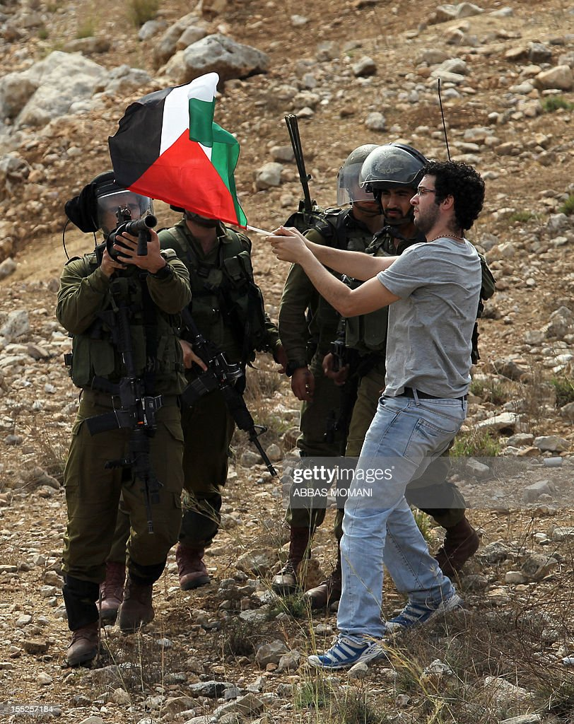 A demonstrator waves a Palestinian flag in front of Israeli soldiers during a protest against the confiscation of Palestinian land in the West Bank village of Nabi Saleh near Ramallah on November 2, 2012.