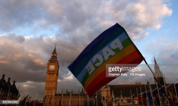 A demonstrator waves a peace flag at Parliament Square London in protest against Britains trident weapons system vote which is taking place today