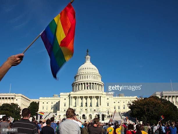 A demonstrator waves a rainbow flag in front of the US Capitol in Washington on October 11 2009 as tens of thousands of gay activists marched to...