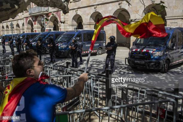 A demonstrator waves a Spanish national flag in front of members of the Mossos d'Esquadra the Catalan police force during a protest for Spanish unity...