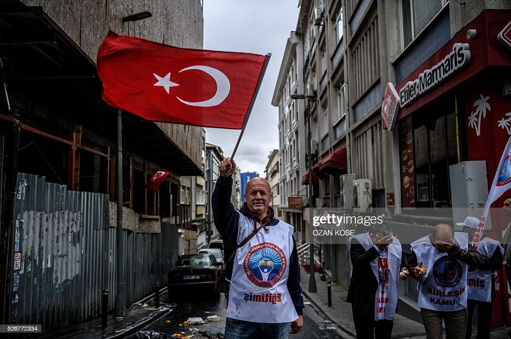 A demonstrator waves a Turkish flag during a May Day rally in Sisli, a district of Istanbul, on May 1, 2016. Turkish labour activists and leftists marked the annual May Day holiday, with thousands of security deployed and bracing for trouble after the authorities refused to allow protests in central Taksim Square. / AFP / OZAN