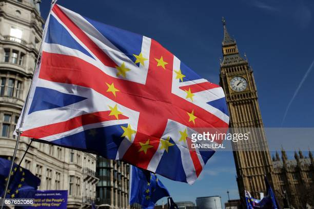 A demonstrator waves a Union flag with the stars of the EU flag as they gather in front of the Houses of Parliament in Parliament Square following an...