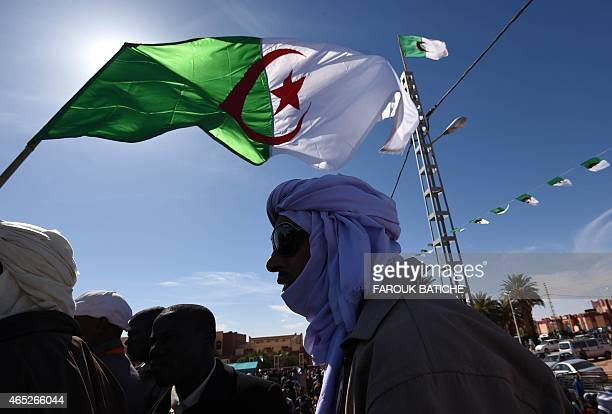 A demonstrator waves an Algerian flag during a sitin on March 5 2015 at Somoud Square in the Sahara desert village of InSalah south Algeria to...