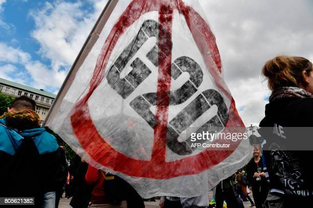 TOPSHOT A demonstrator waves an antiG20 banner during a demonstration called by several NGOs ahead of the G20 summit in Hamburg on July 2 2017 / AFP...