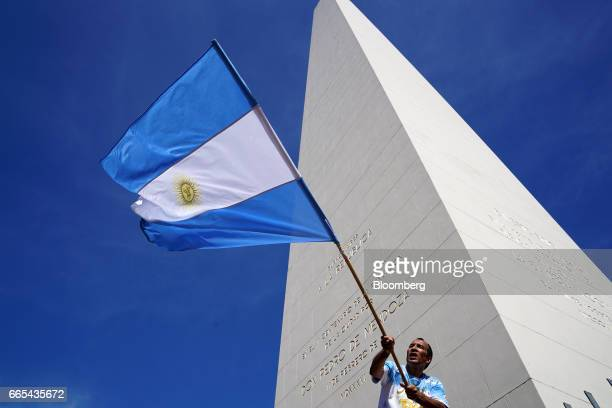 A demonstrator waves an Argentinian flag in front of the Obelisk monument during a national strike in Buenos Aires Argentina on April 6 2017...
