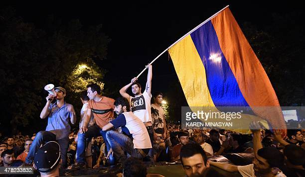 A demonstrator waves an Armenian flag during a protest against an increase of electricity prices in the Armenian capital Yerevan on June 23 2015...