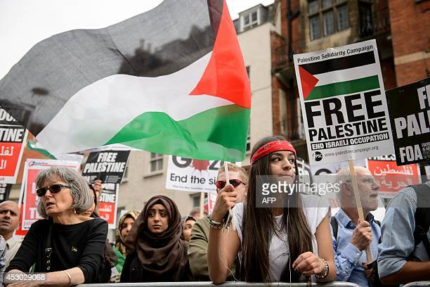 A demonstrator waves the Palestinian flag during a protest near the Israeli embassy in central London on August 1 calling for an end to Israel's...