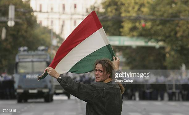 A demonstrator waving a Hungarian flag looks back while confronting police during violent street protests October 23 2006 in Budapest Hungary The...