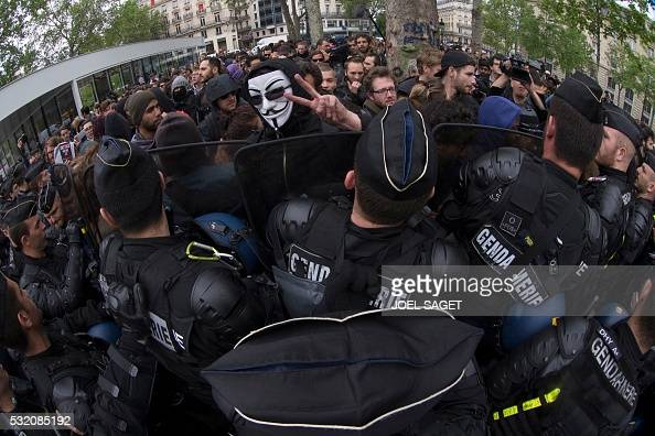 TOPSHOT A demonstrator wearing a Guy Fawkes mask gestures as demonstrations clash with police during a counterdemonstration to a rally of police...