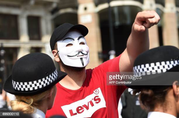 A demonstrator wearing a Guy Fawkes mask gestures during a protest in Parliament Square in London on June 21 during an antigovernment protest to...