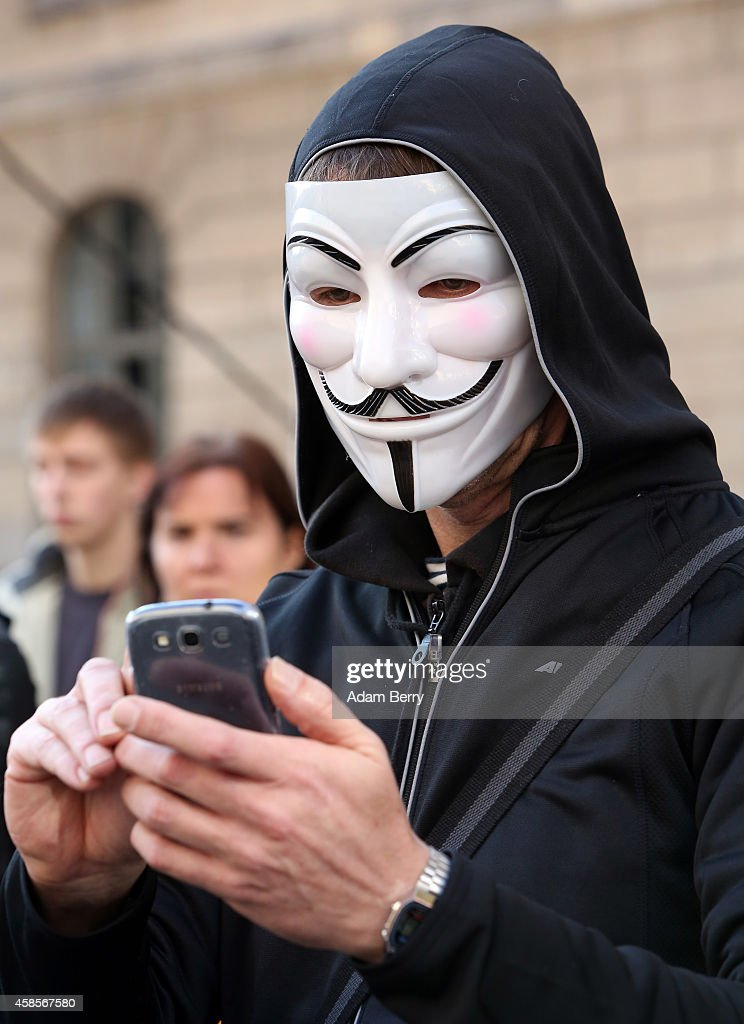 A demonstrator wearing a <a gi-track='captionPersonalityLinkClicked' href=/galleries/search?phrase=Guy+Fawkes&family=editorial&specificpeople=101029 ng-click='$event.stopPropagation()'>Guy Fawkes</a> mask uses a mobile phone as he protests the German and European governments' treatment of refugees at the launch of two buses full of activists traveling from Berlin to the Mediterranean to 'Tear down the European Wall,' or cut down portions of the European Union's border fence, on November 7, 2014 in Berlin, Germany. Amidst ongoing celebrations for the 25th anniversary of the Fall of the Berlin Wall, activists from the group Center for Political Beauty (CPB, or Zentrum fuer Politische Schoenheit, ZPS, in German) claim to have removed 14 white crosses from the city center placed in memory of some of the victims killed trying to cross from East to West Berlin during the Cold War, a protest designed to call attention to the activists' perceived hypocrisy found in fortifying the border preventing entry for refugees into Europe while celebrating the fall of the notorious one in Berlin a quarter of a century ago. The artist collective claims to have given the crosses to refugees from Mali hiding in the forests of Mount Gurugu in northern Morocco who are trying to cross into Melilla, one of two Spanish enclaves in the region, for passage into Europe.
