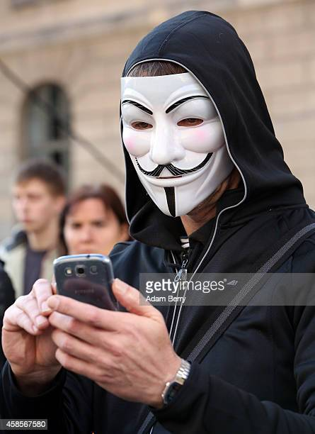 A demonstrator wearing a Guy Fawkes mask uses a mobile phone as he protests the German and European governments' treatment of refugees at the launch...